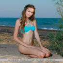 Elle Tan playfully strips at the sandy beach as she strips her bikini.