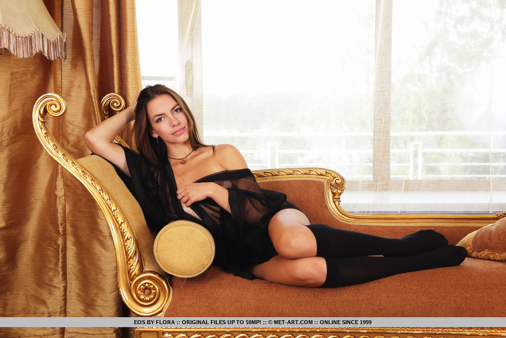 Eos smiles sweetly as she reclines in the couch to striptease