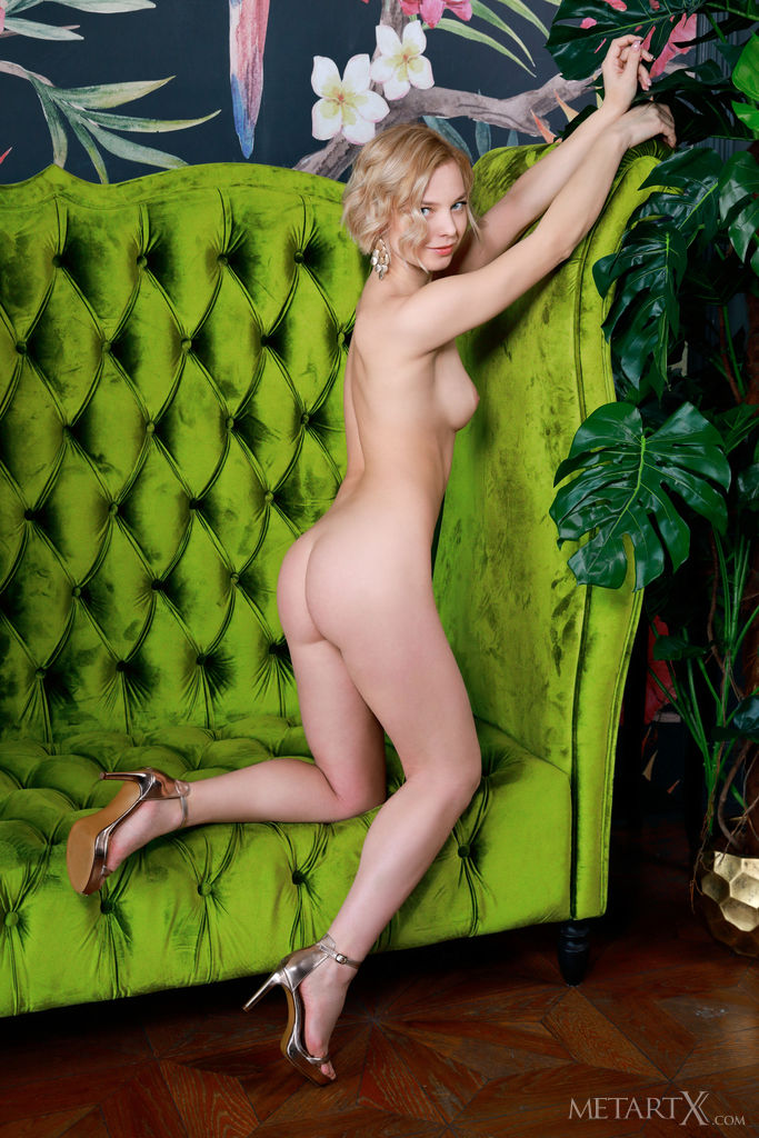 Hilary Wind's long and slender physique, smooth, porcelain skin, and provocative poses stands out against the luxurious green sofa