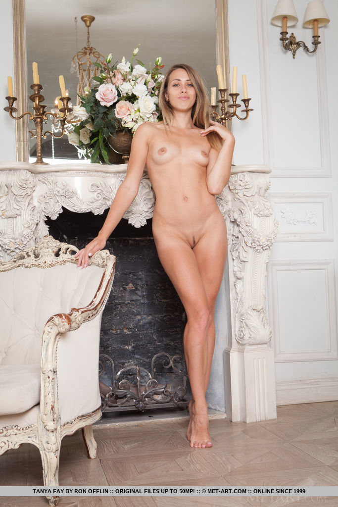 Tanya Fay shows off her naked, slender body and trimmed pussy on the couch.