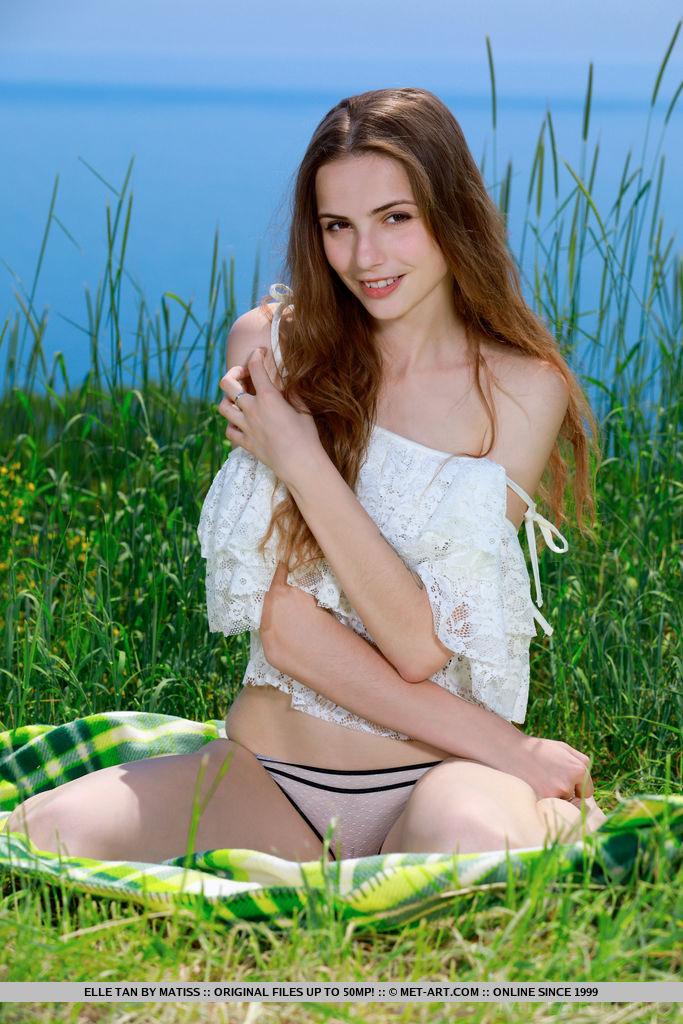 Elle Tan bares her slender body as she playfully poses on the grass.