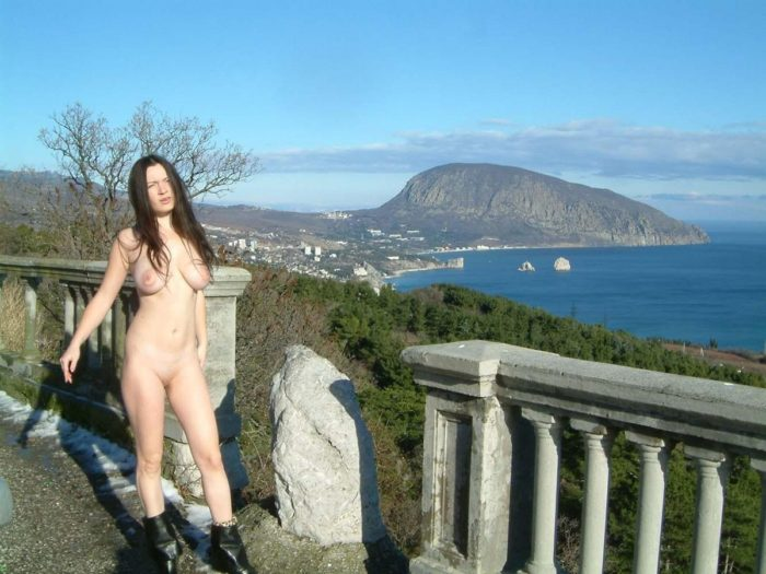 Young busty brunette posing at beautiful viewpoint