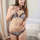 A cheerful, vivacious smile on her pretty face, amplifying her girly appeal, Taissa A haves fun stripping off her matching lingerie to reveal her nubile body.