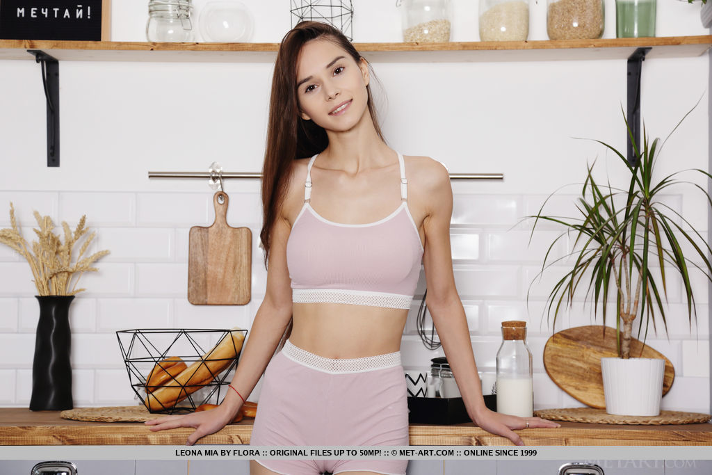 Amazing model Leona Mia bares her tight body and sweet pussy in the kitchen.