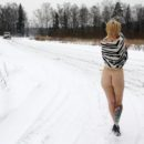 Blonde undresses on the side of the winter road