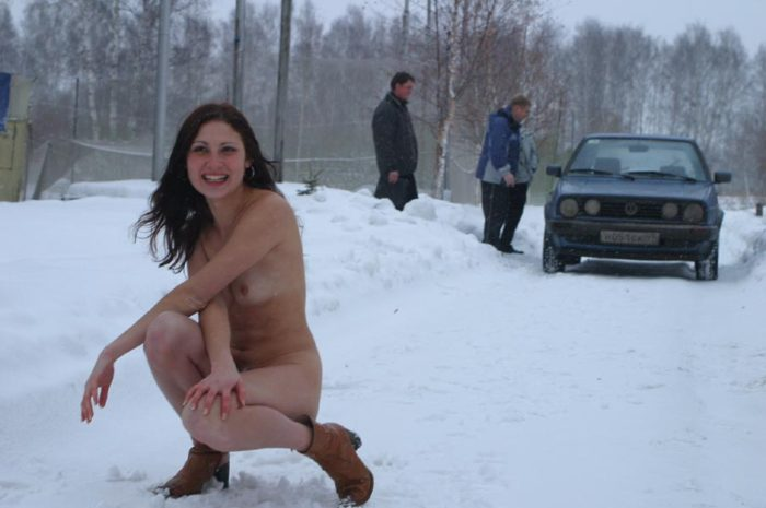 Brunette in leather boots on a snowy road