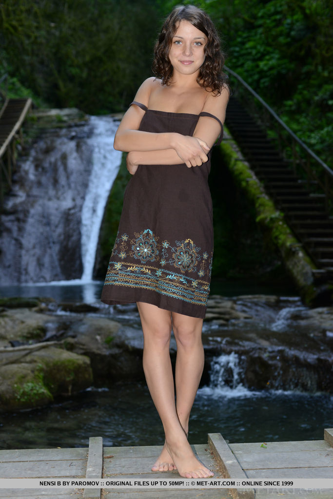 Cute Nensi B showcasing her delightfully petite body against a refreshing view of the cascading waterfalls.