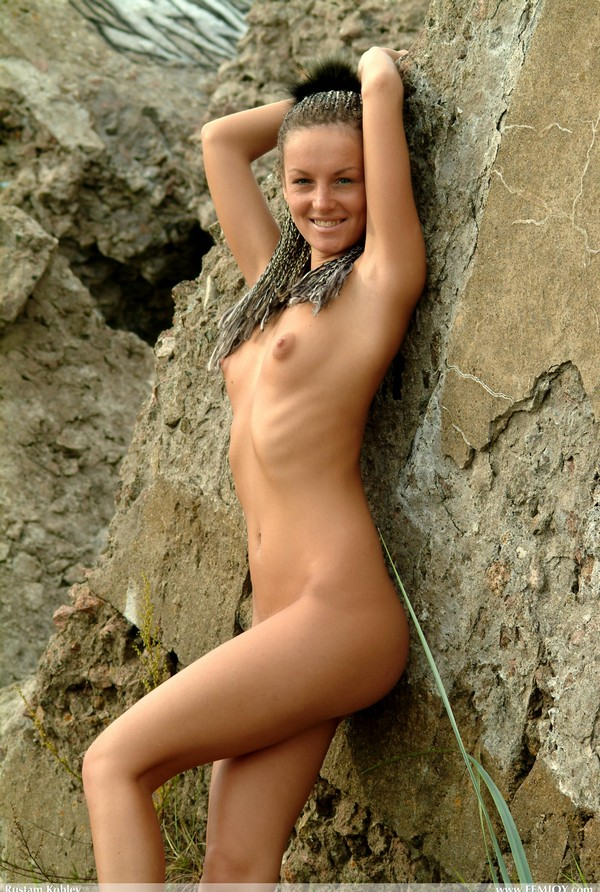 Girl with dreadlocks posing naked on the rocks