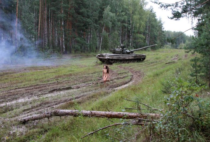 Long-haired russian girl posing at tank test site