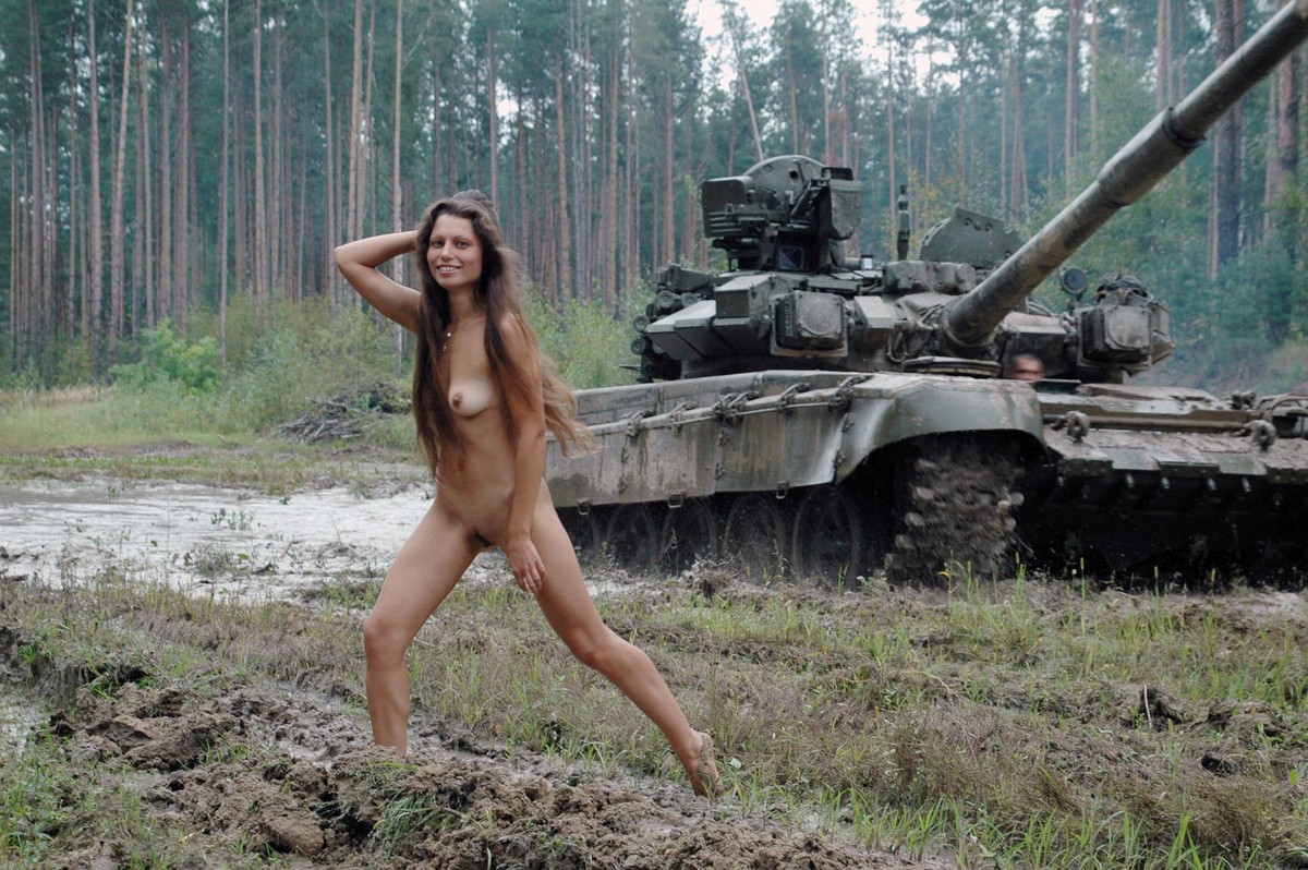 Long-haired russian girl posing at tank test site ...