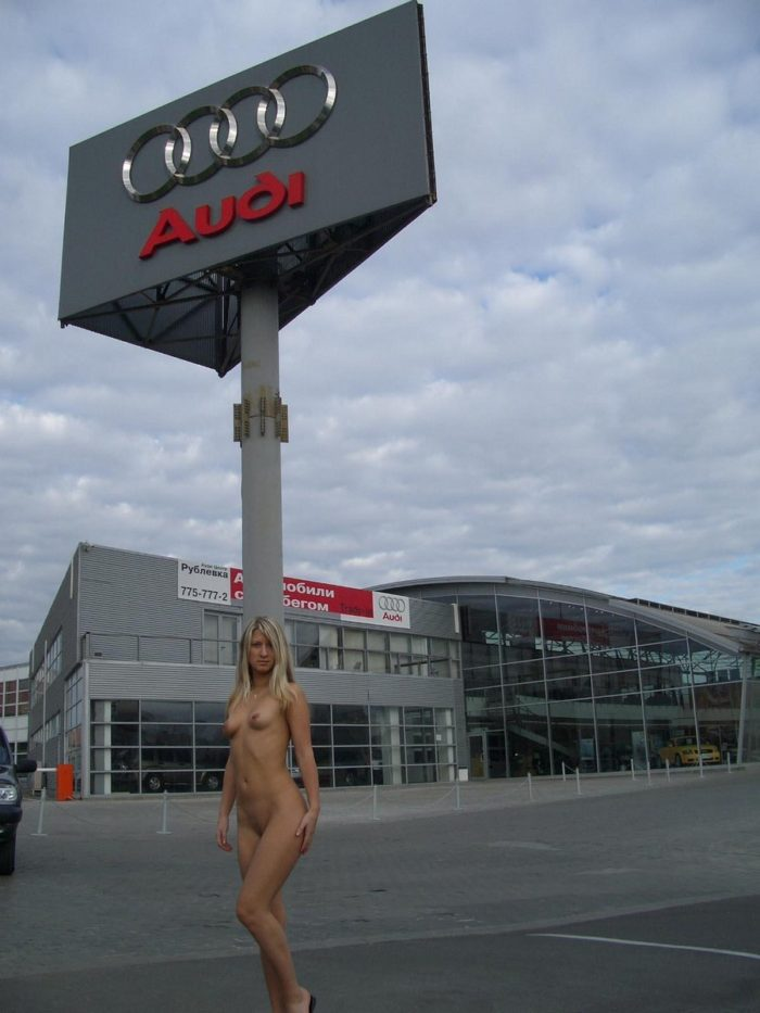 Naked blonde girl at the mall parking