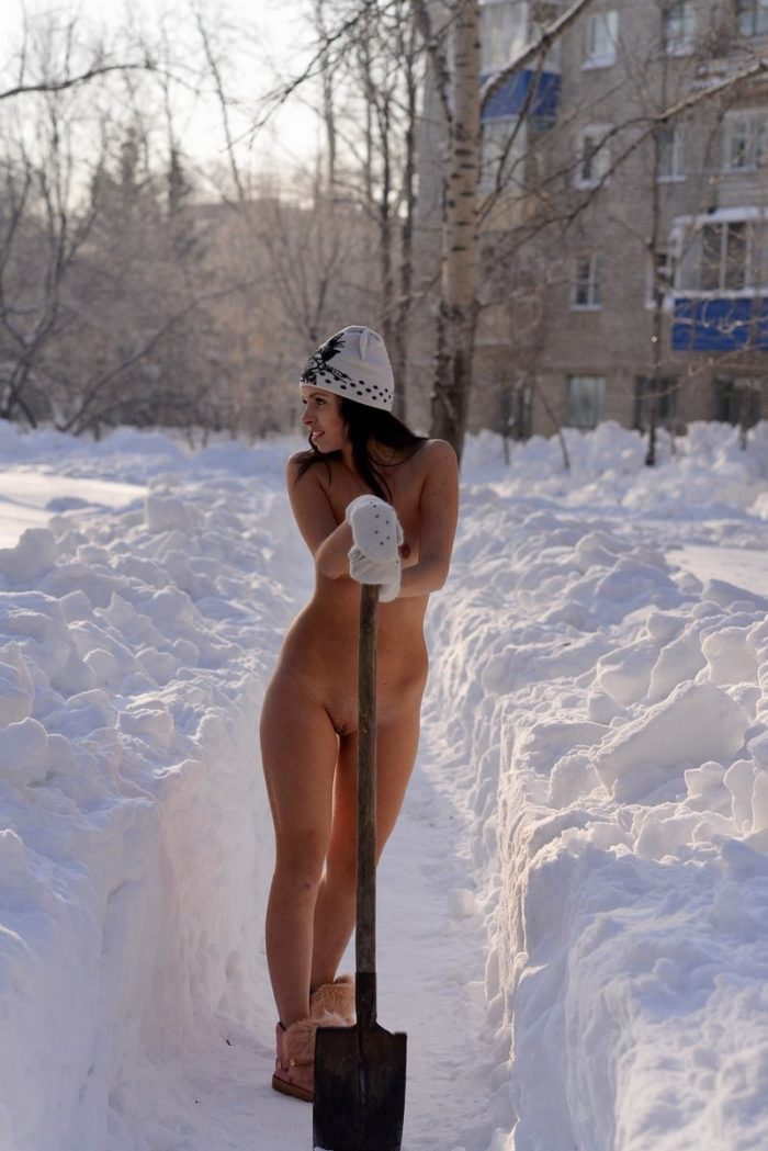 Naked girl in boots clears snow on the track