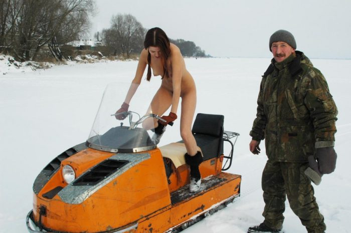 Naked girl riding a snowmobile