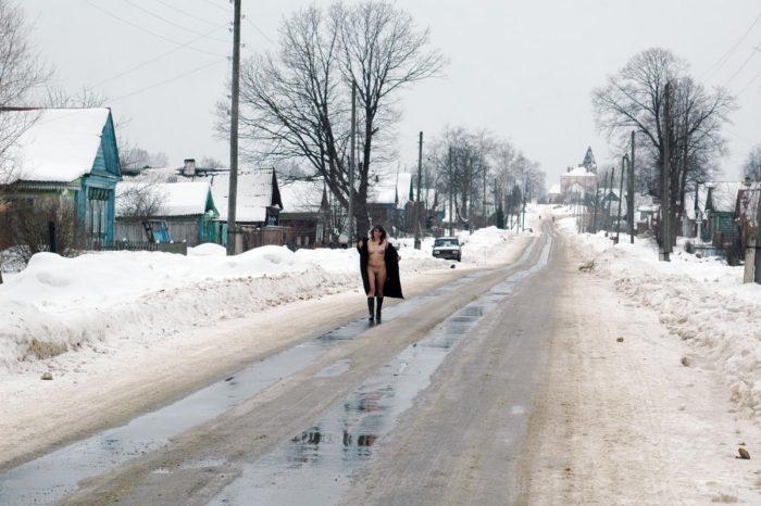 Naked girl walks on the winter road