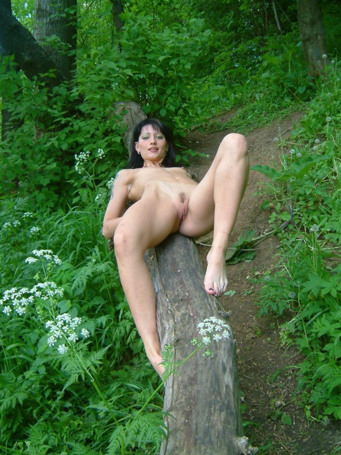 Naughty brunette touches her pussy in the woods
