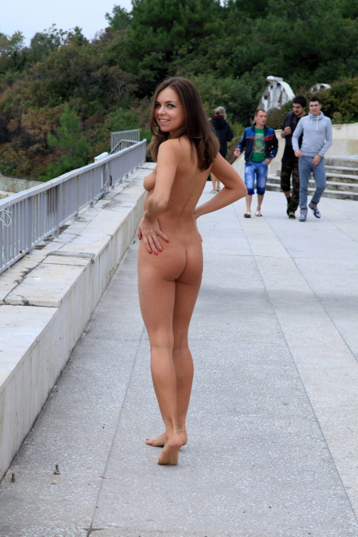 Pretty girl walks naked in the morning along the city embankment
