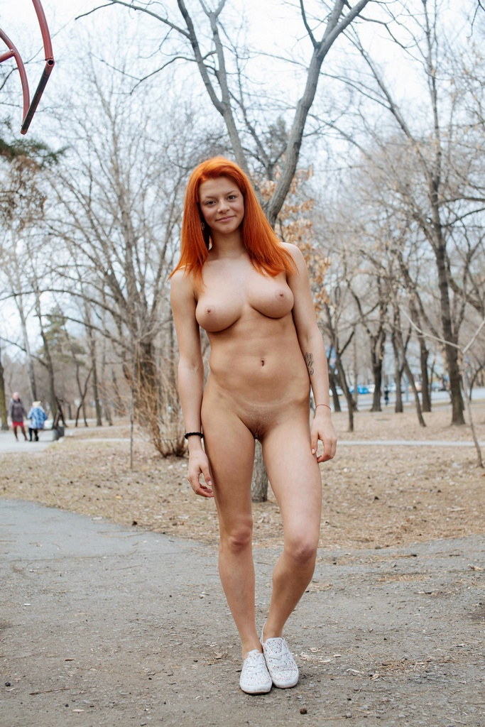 Red-haired girl doing gym exercises on the playground