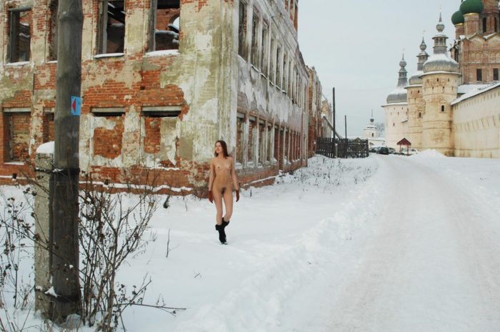 Redhead girl wears only boots and gloves at winter streets