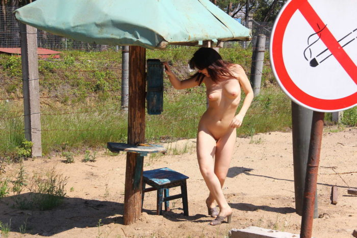 Russian girl undresses near military facility