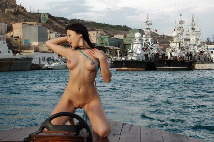 Young brunette on a boat shows her body to sailors