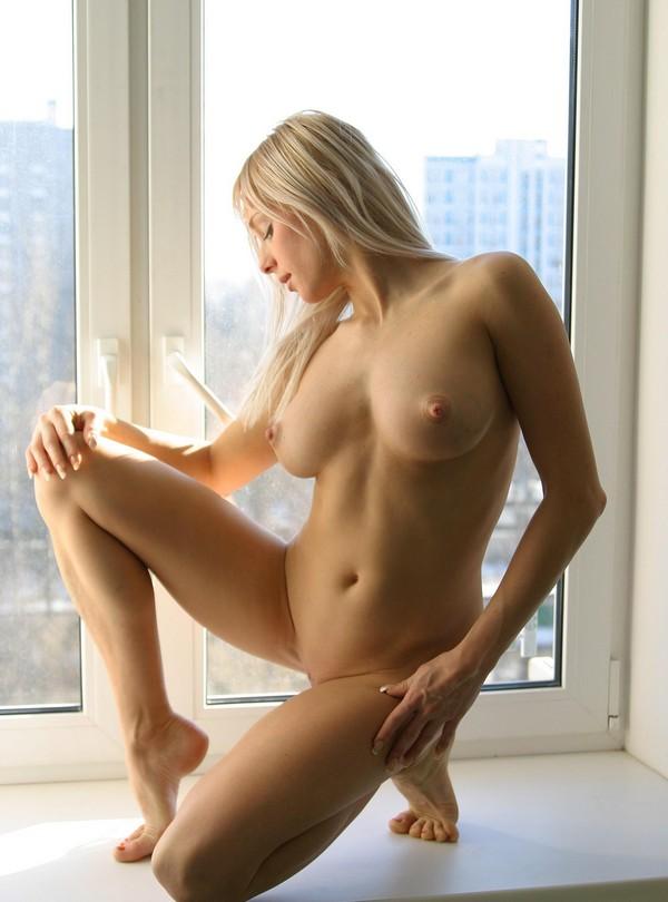 Amateur blonde posing on kitchen windowsill