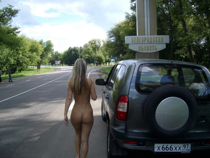 Blonde posing next to the car on the road
