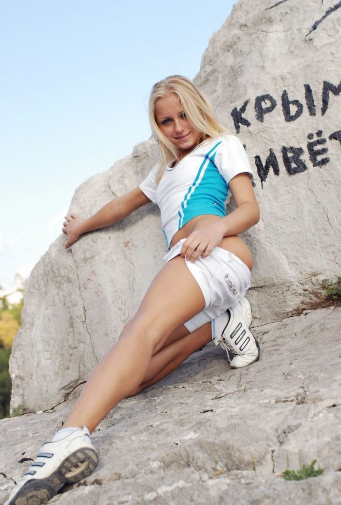 Blonde takes off white shorts on the rocks