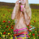 Kendell	delightfully poses in the flowery field baring her creamy body.