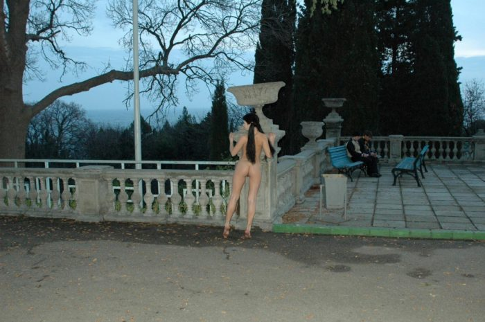 Naked busty girl walks around the sights