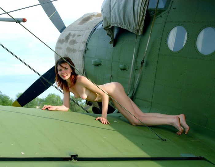 Naked girl on the wing of an old plane