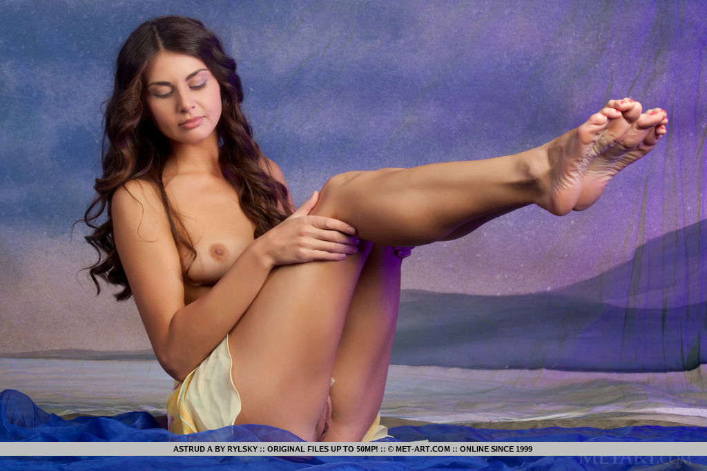 Naturally beautiful Astud A with slighly tanned, even complexion, and toned physique poses against a dreamy blue background, bending and posing her athletic body.