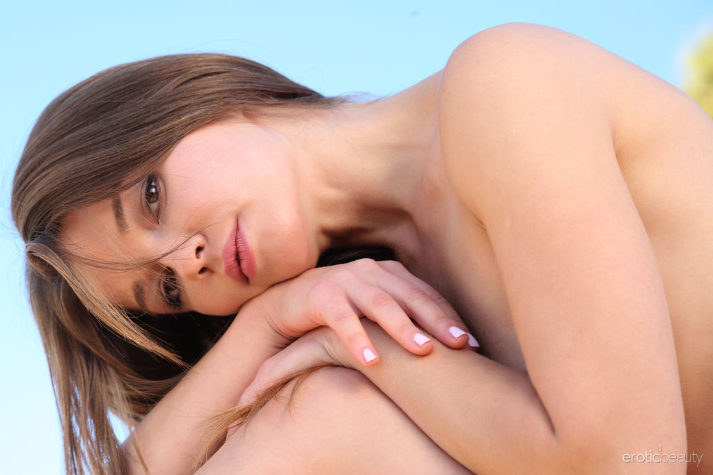 Nedda A displays her naked, petite body as she poses outdoors.