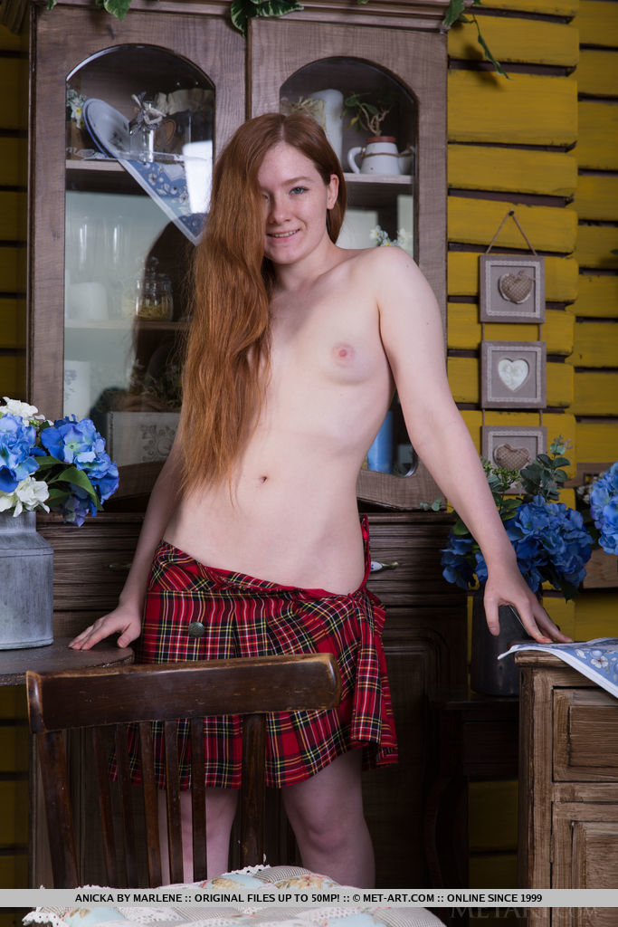 Redhead Anicka flaunts her small tits and meaty ass as she strips in front of the camera.