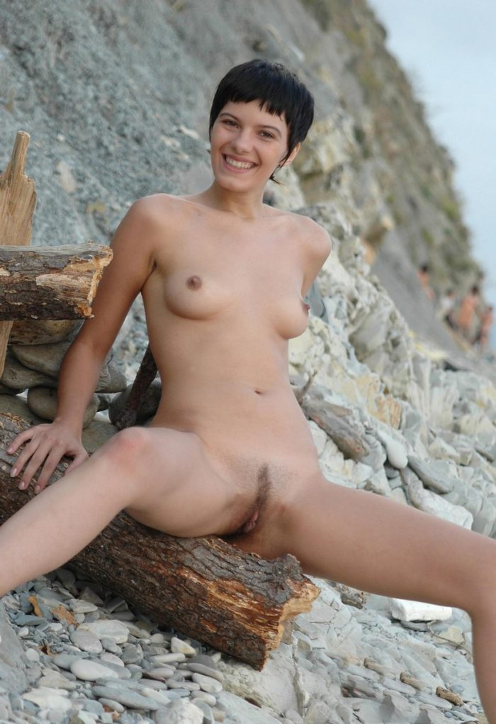 Short-haired brunette shows pussy with a smile onrocky beach