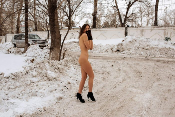 Smiling girl walks on winter streets in boots and mittens