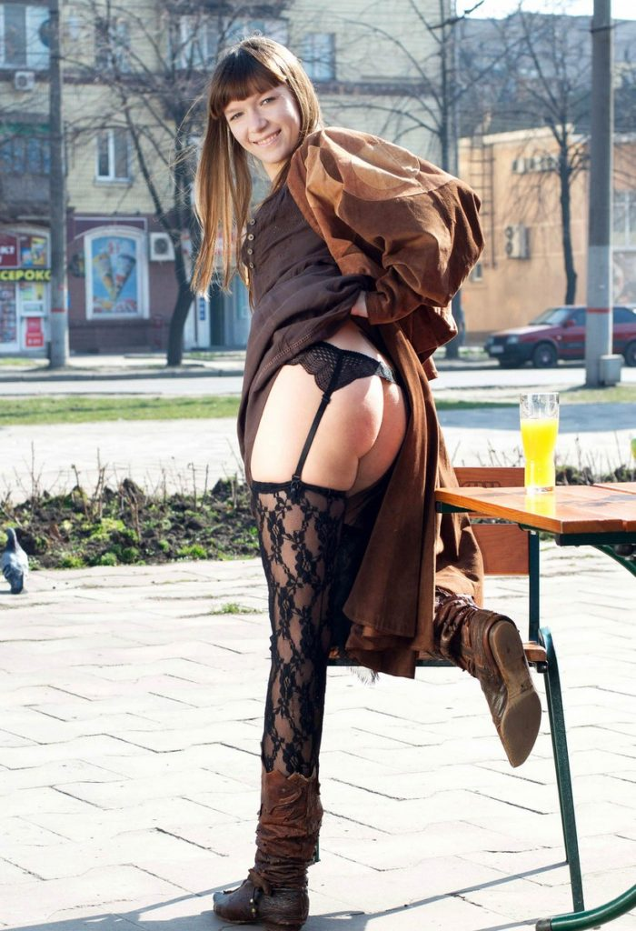Smiling teen posing at streets in sexy stockings