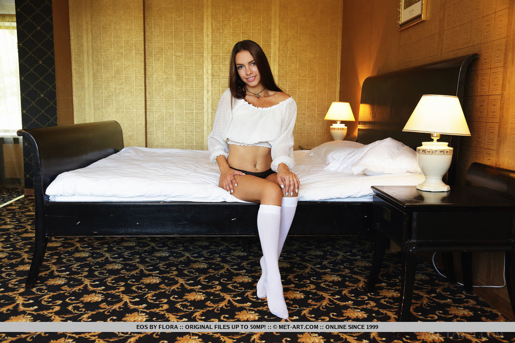 Eos plays with erect nipples as she sensually strips on the bed.