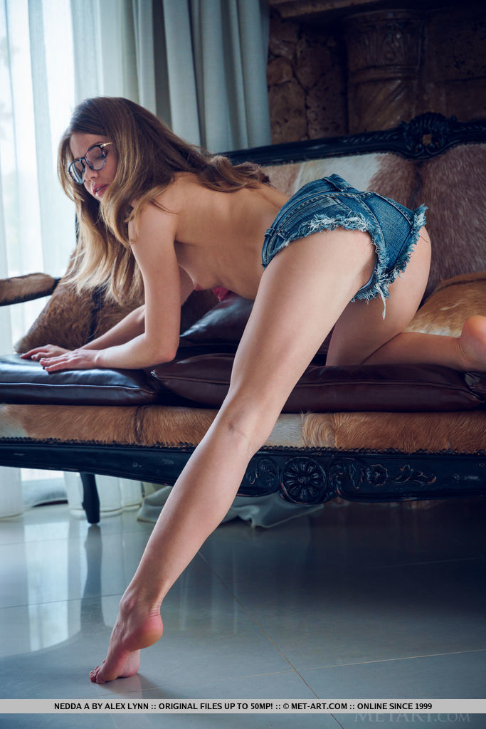 Nerdy Nedda A bares her tight body and sweet pussy as she strips on the couch.