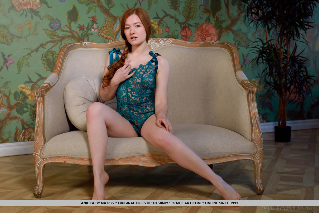 Redhead Anicka displays her creamy body and hairy pussy on the couch.
