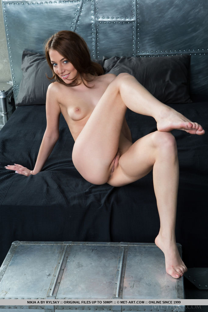 Wearing a warm, charming smile on her pretty face, Nikia A highlights her long, svelte legs, tight butt, and smooth pussy with cute trimmed bush.