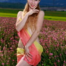 Kendell poses among the flowers baring her creamy, slender body.