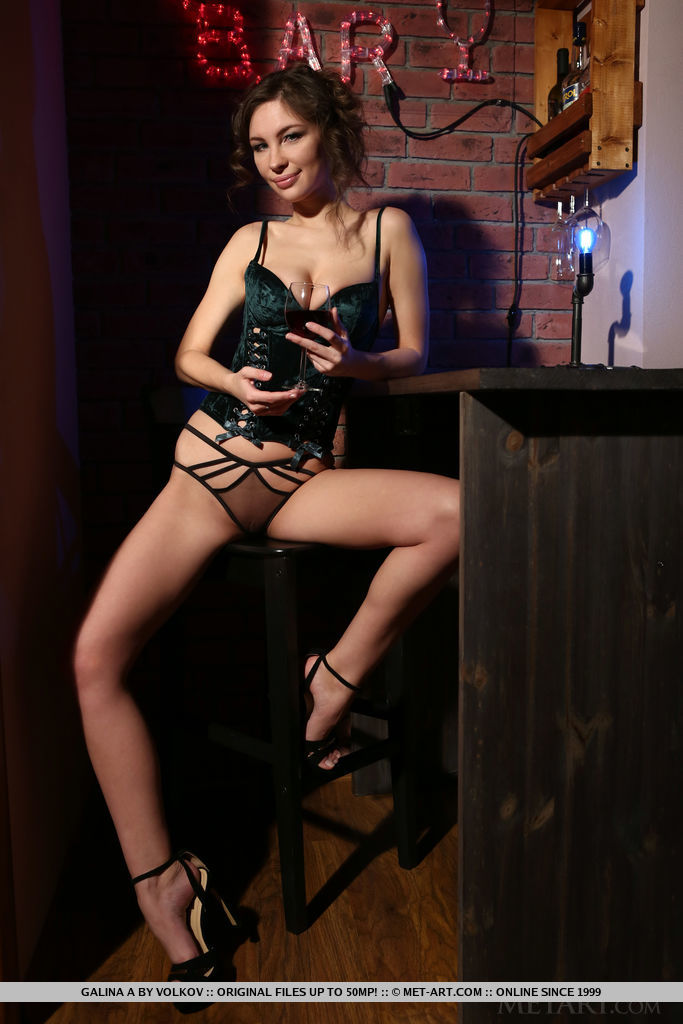 Galina A strips her black corset as she sensually poses at the bar.