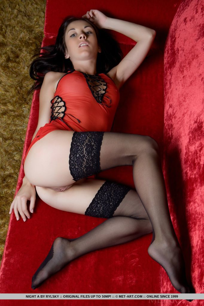 Night A s lean legs garbed in sheer black stockings while her body is wrapped in silky red lingerie dress as she poses sensually on top of the sofa