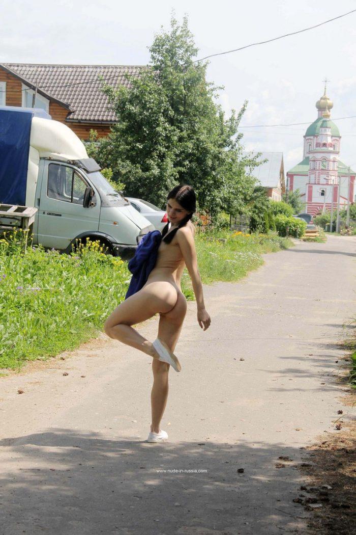 Slim brunette Daria walks at village road