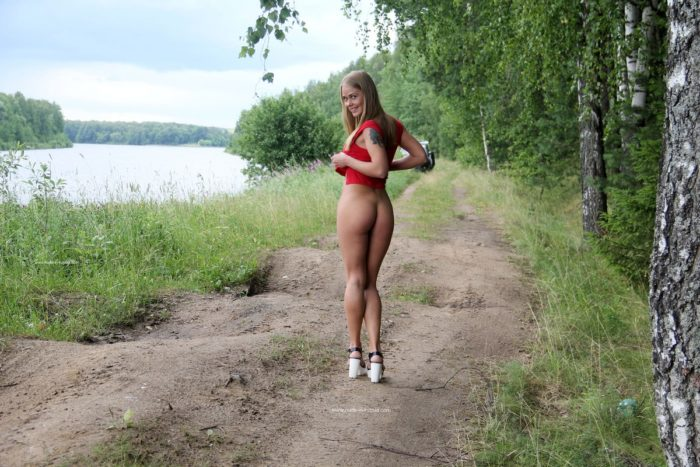 Smiling blonde removes her red dress outdoors