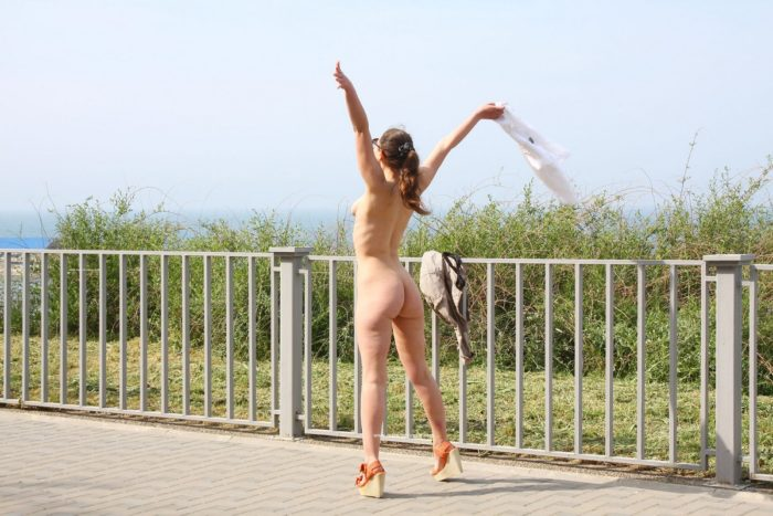 Smiling russian girl walks naked at public park