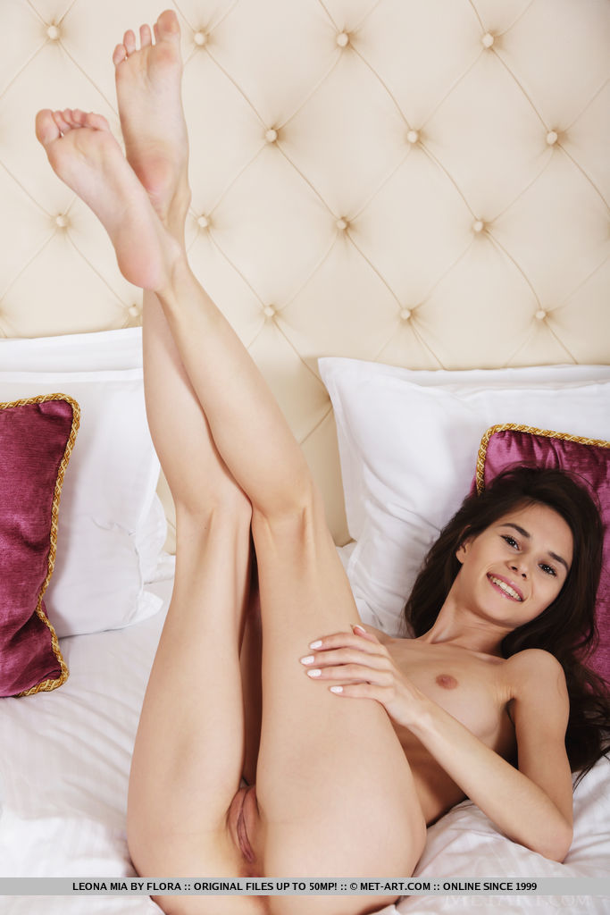 Top model Leona Mia bares her delectable pussy as she poses on the bed.