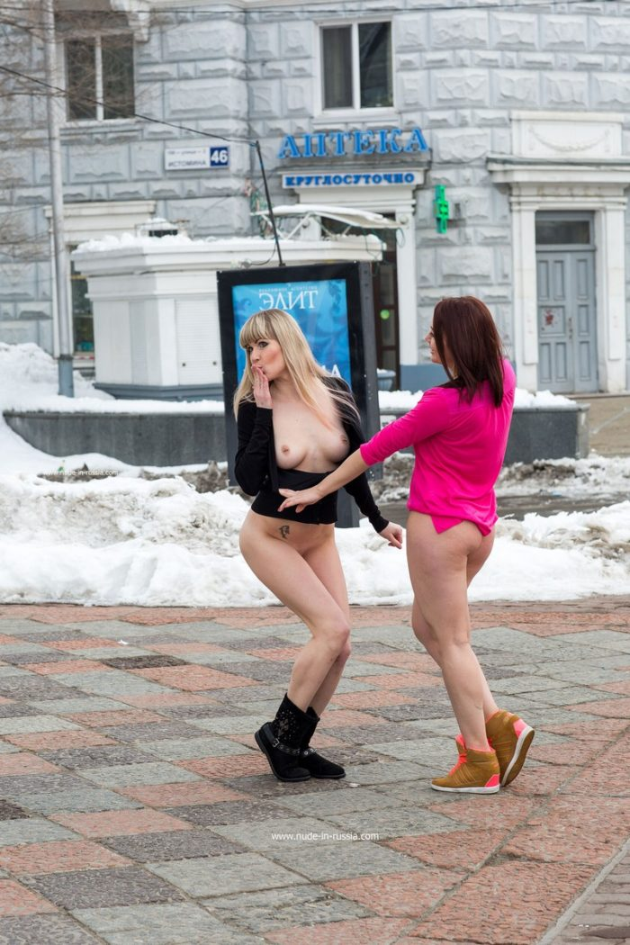 Two crazy babes play with snow at city center