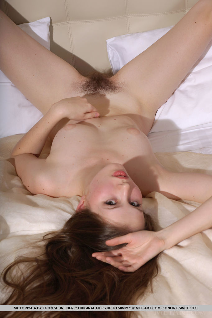 Victoriya A s lusty and enticing body sprawled on top of the bed, with a majestic view of sweet and ripe pussy and unshaved bush, long and smooth legs, and puffy, cuppable breasts.
