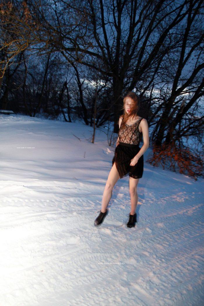 Nude girl riding on snow saucer